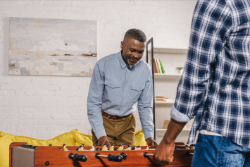 An adult father and son happy playing foosball