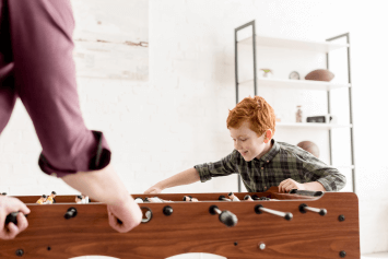 A child and an adult playing foosball
