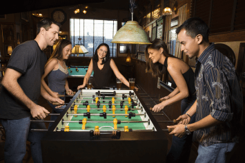 A group of friends playing foosball in a pub