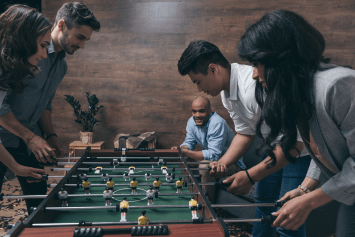 A group of friends playing foosball