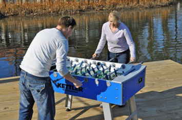 Two people playing on a Kettler foosball table outside