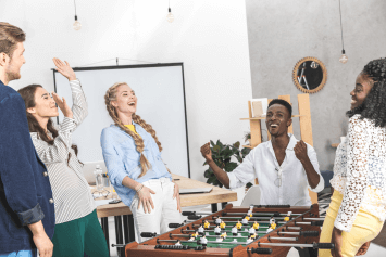 Men and women playing foosball in an office