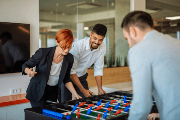 Business people playing foosball in the office